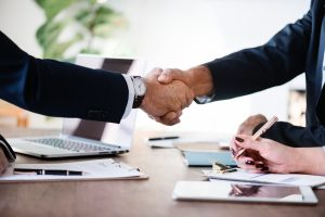 Two men shaking hands, after signing a contract. A good way to avoid property damage is to hire professionals.
