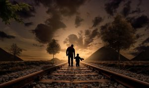 A father and son walking on the rails.