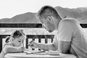 A father and daughter writing.