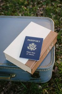 A suitcase, a book and American passport needed for moving to Canada