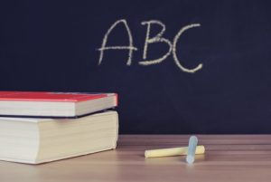 There is a blackboard, two books and two chalks. And on the blackboard there are three letters written down, A, B and C.