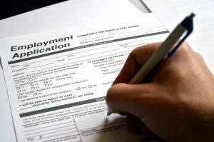 Aperson filling in an employment application.