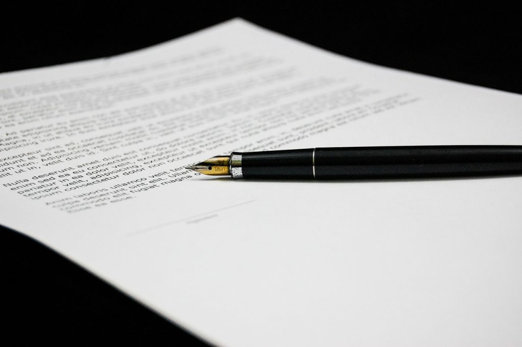 A document and a pen symbolizing all the paperwork you need to prepare for doing business with Saudi Arabia.