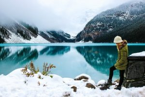 A girl standing by a lake in winter.