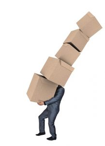 A man in a suit carrying a pile of cardboard boxes.