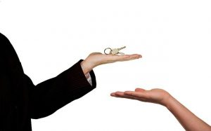 A real estate agent handing over the keys to the client once the process of buying a property in Canada comes to its end.