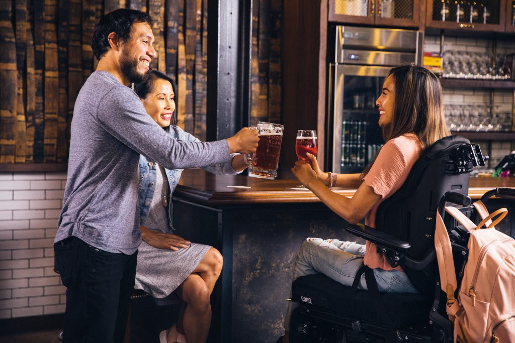 Three young friends sitting in a bar drinking  and laughing