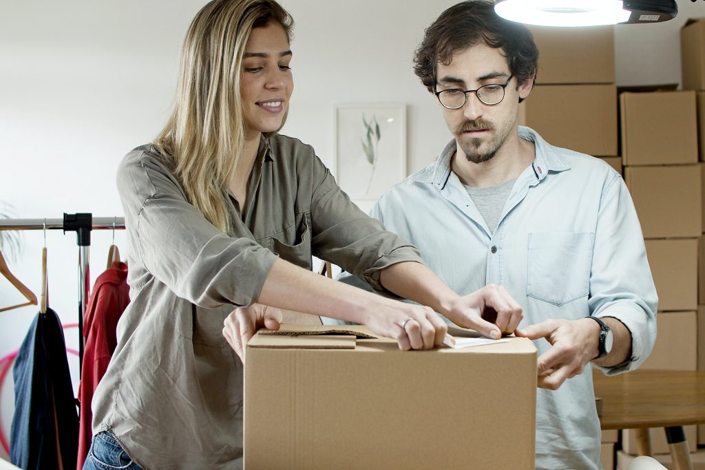 woman and a man following a timeline for a moving day while packing