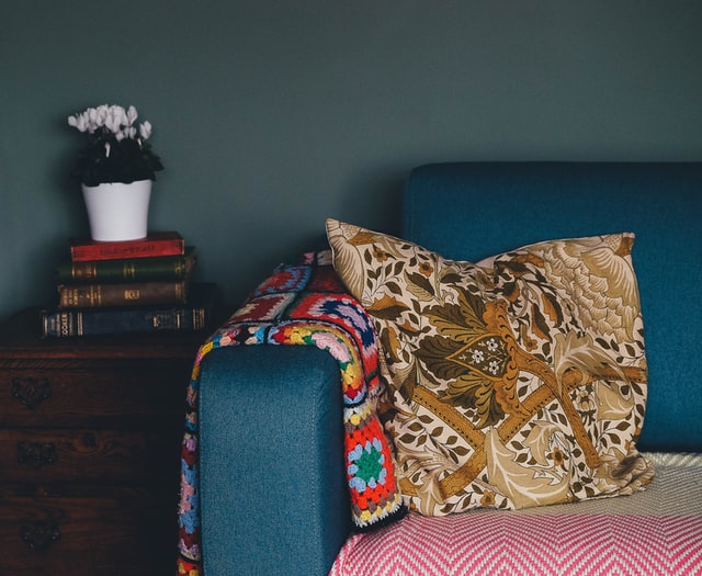 A brown pillow on the blue couch beside a pile of books