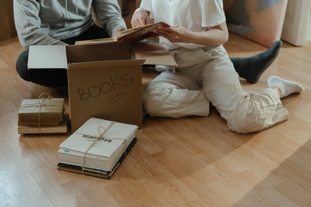 Man and woman openning boxes with books and trying to speed up unpacking.