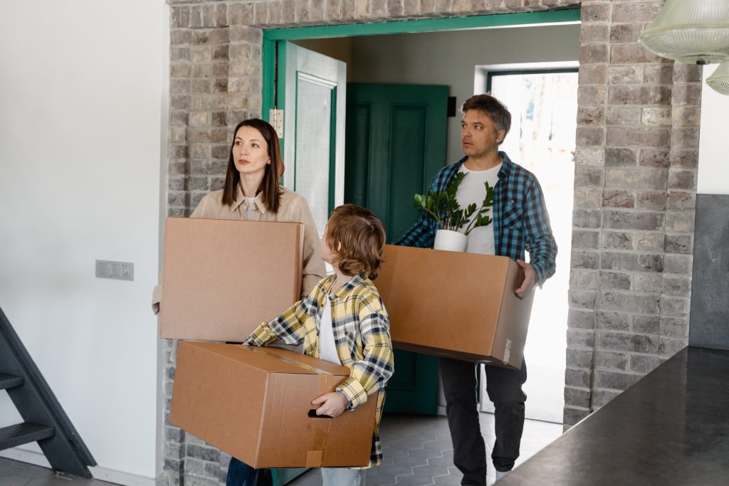 Parents and a kid carrying boxes into a new home and looking how to speed up unpacking.