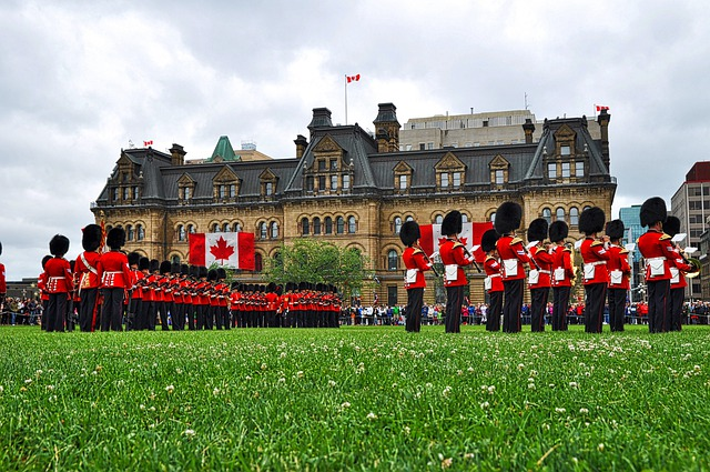 People wearing Canadian Uniform on a meadow in front of a building.