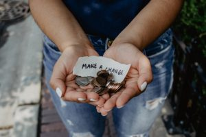 person showing both hands with a make a change note and some coins