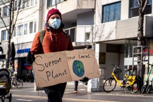 man holding a sign support your local planet