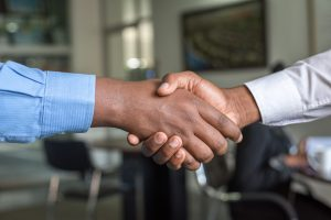 A handshake after finding professional assistance for buying a house in new Jersey.